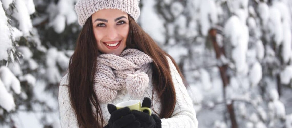 Pretty girl in the woods in winter background with tea cup. Beautiful cheerful woman drinking coffee outdoors. Close up portrait of a beautiful lady
