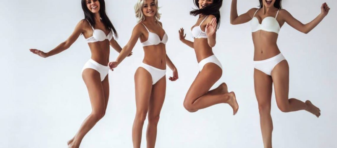Group of young sexy multiracial women in white lingerie are posing and jumping on white background. Attractive women isolated.