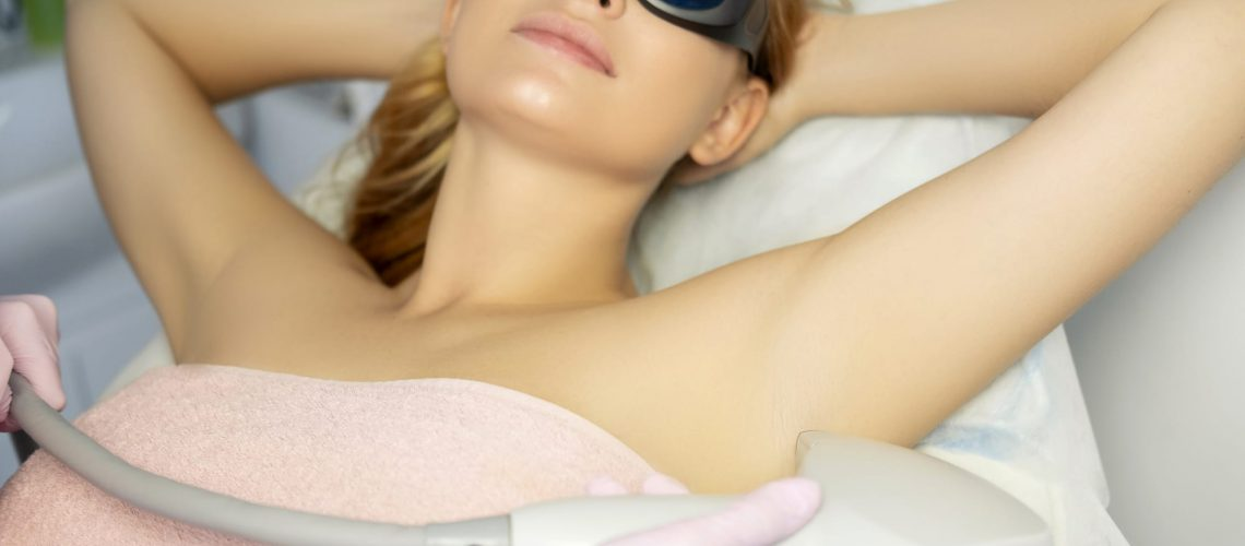 Woman doctor cosmetologist removing hair from a woman client body using laser epilator. They in a spa center.